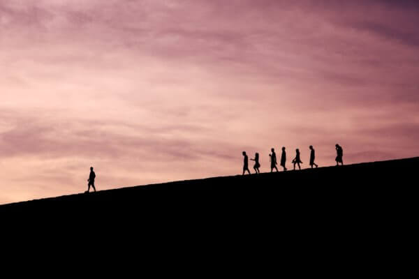 Silhouette of people on hill following each other